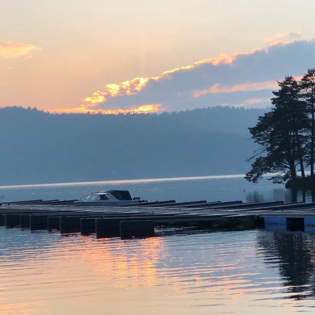 Solnedgang over Farris. Molo med båt, noen trær, en åsrygg i det fjerne. Sola har nettopp gått ned.